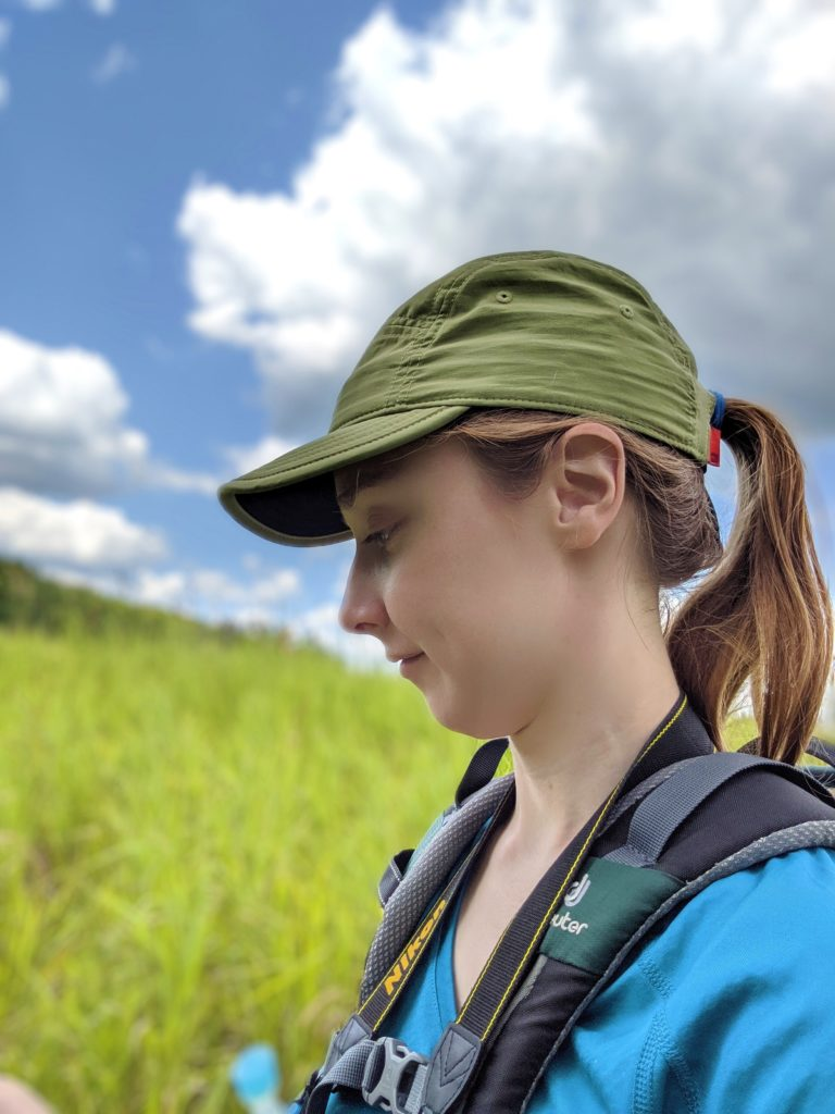 Amanda Liczner, ecologist, looking for bumble bees in a grassland on a sunny day